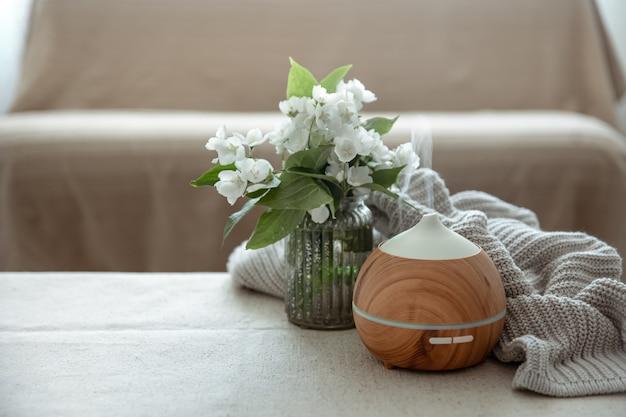 Difusor moderno de aroma de óleo na sala de estar sobre a mesa com elemento de malha e flores