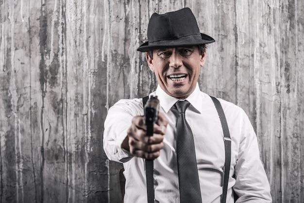 Diga adeus! homem sênior autoritário com roupas de gângster estendendo a mão com a arma e encostado na parede cinza