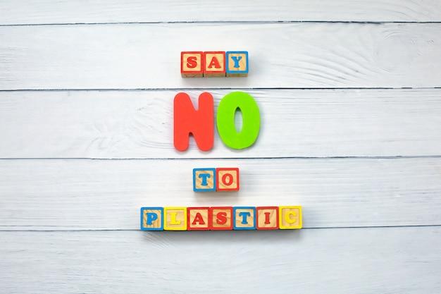 Diga não ao plástico em cubos de madeira no fundo de madeira.