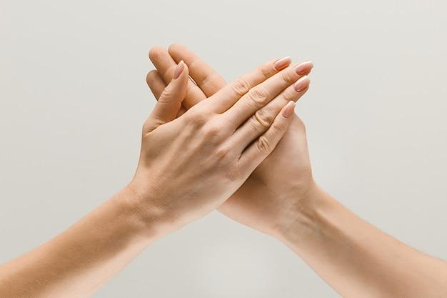Diga olá para as novas reuniões. mãos masculinas e femininas, demonstrando um gesto de conseguir contato ou saudações isoladas no fundo cinza do estúdio. conceito de relações humanas, relacionamento ou negócios.