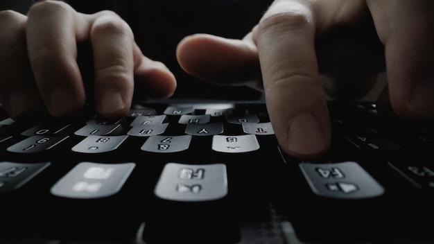 Digitação de dedo em foco suave em close-up no teclado. mão de homem usando laptop no escritório