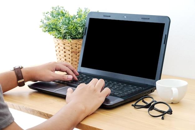 Digitação manual no laptop com tela em branco para a maquete acima