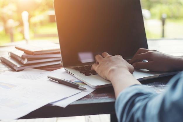 Digitação mão da mulher de negócios no teclado do portátil com cha financeiro