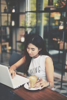 Digitação rapariga em seu computador enquanto tomando café