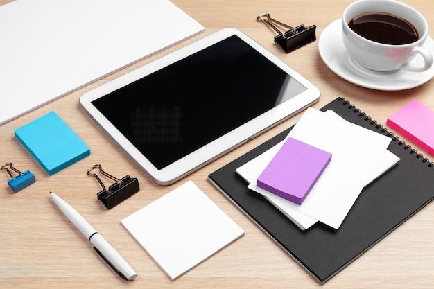 Digital tablet com bloco de notas, suprimentos e xícara de café na área de trabalho.
