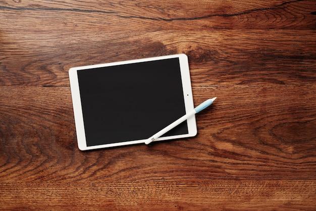 Digital tablet e lápis sobre uma mesa de madeira.