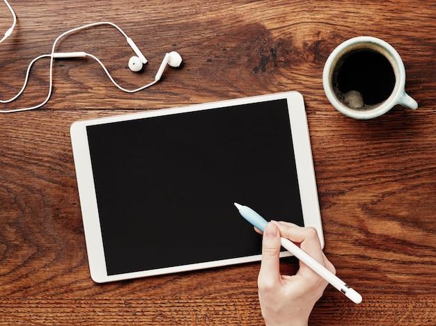 Digital tablet e xícara de café em uma mesa de madeira. lápis na mão.