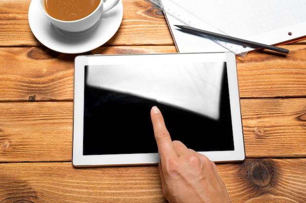 Digital tablet e xícara de café na mesa de madeira