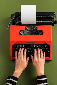 Digitando em um papel em branco de uma máquina de escrever retrô vermelha