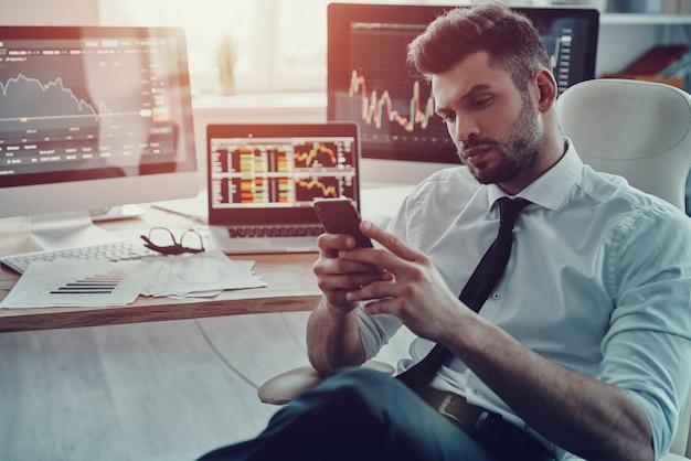 Digitando mensagem de negócios. jovem empresário pensativo em trajes formais usando seu telefone inteligente enquanto está sentado no escritório