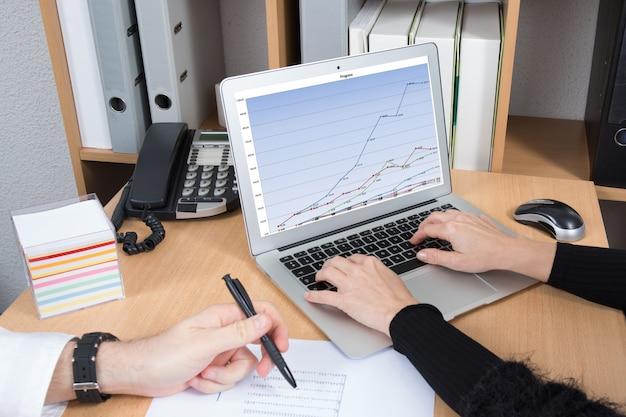Digitando no laptop enquanto o homem escreve no relatório