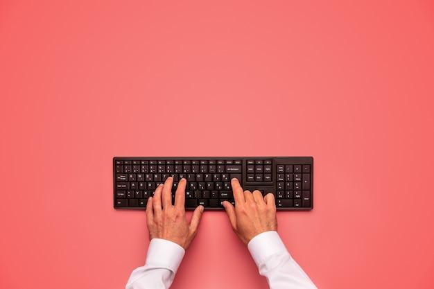 Digitando no teclado do computador preto sobre a mesa rosa