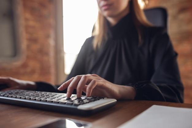 Digitando texto, close-up. mulher jovem caucasiana em traje de negócios, trabalhando no escritório. jovem empresária, gerente fazendo tarefas com smartphone, laptop, tablet tem conferência online. finanças, trabalho.