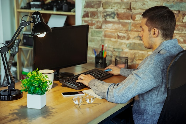 Digitando texto. homem que trabalha em casa durante a quarentena de coronavírus ou covid-19, conceito de escritório remoto. jovem empresário, gerente fazendo tarefas com smartphone, computador, tem conferência online, reunião.
