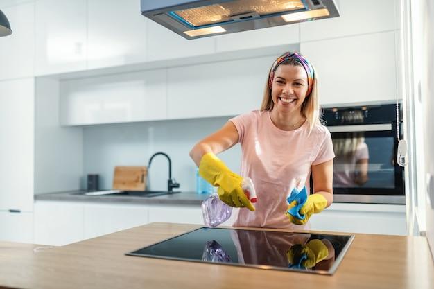 Digna dona de casa alegre com luvas de borracha, pulverizando fogão e limpando com desinfetante