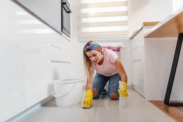 Digna dona de casa loira arrumada ajoelhada na cozinha e limpando o chão.