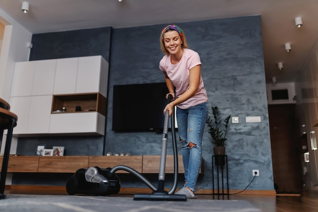 Digna dona de casa sorridente arrumada usando aspirador de pó para aspirar o pó no tapete na sala de estar.
