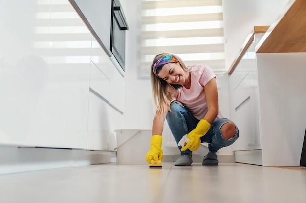 Digna sorridente dona de casa loira alegre arrumada agachada na cozinha, limpando o chão e assumindo o telefone.