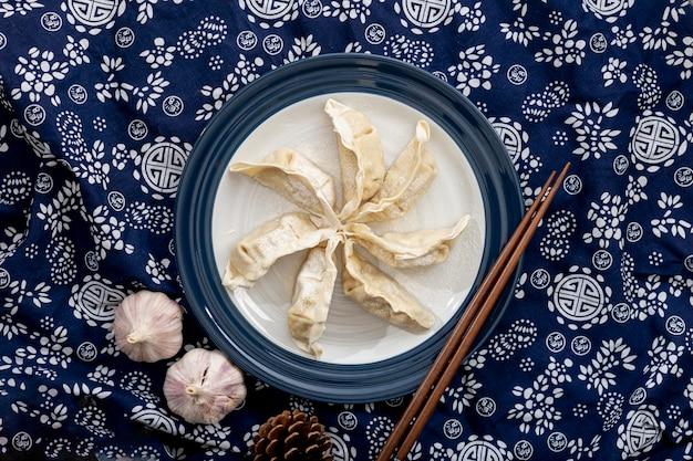 Dim sum em um prato branco com alho em um fundo azul floral