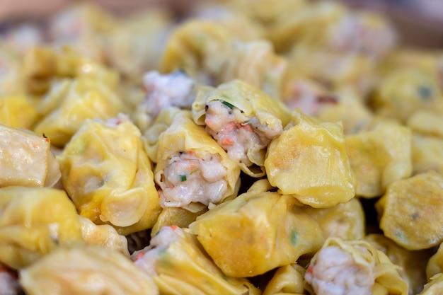 Dimsum cozido no vapor em bambu no mercado de comida de rua na tailândia, close-up. dim sum um prato chinês de pequenos bolinhos salgados cozidos no vapor ou fritos contendo vários recheios, servido como lanche ou prato principal