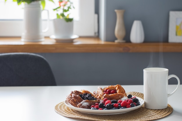 Dinamarquês com framboesas e mirtilos com uma xícara de chá na mesa branca