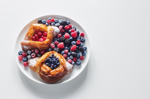 Dinamarquês com framboesas e mirtilos em prato redondo com frutas na mesa branca