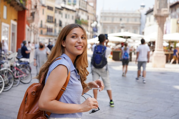Dinâmica garota viajante atraente visita a itália com amigos. mulher jovem e bonita turista fazendo um rápido tour pela europa na empresa.