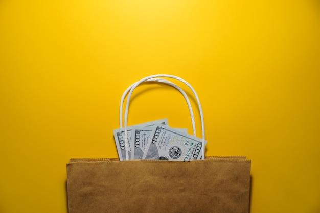 Dinheiro, bolsa em um fundo amarelo, vista superior. dólares em uma sacola de compras. copie o espaço