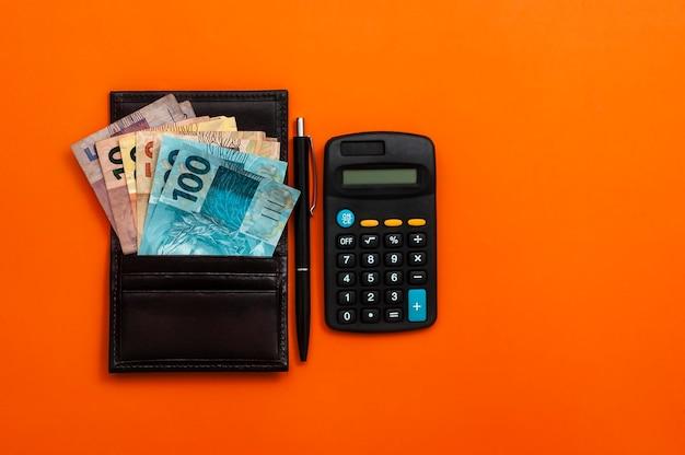 Dinheiro brasileiro em carteira, com bloco de notas, caneta e calculadora.