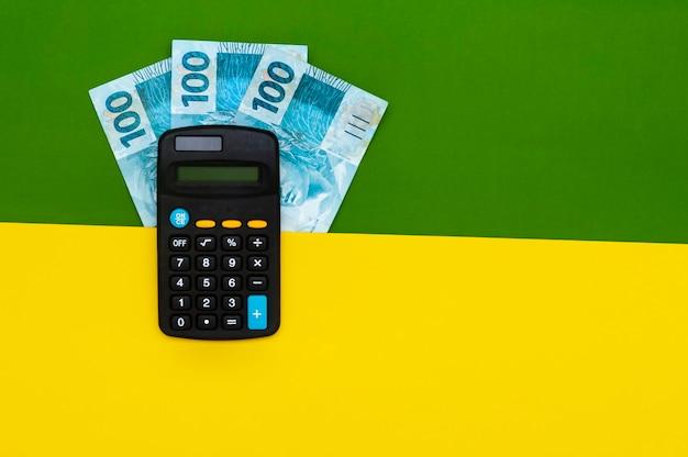Dinheiro brasileiro em carteira, com bloco de notas e calculadora.