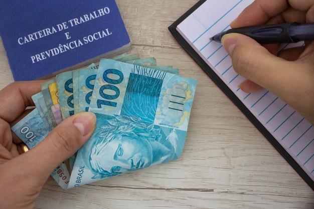 Dinheiro brasileiro em papel cartão fazendo anotações ao lado