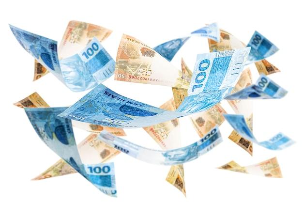 Dinheiro brasileiro fatura 100 e 50 reais, caindo no ar
