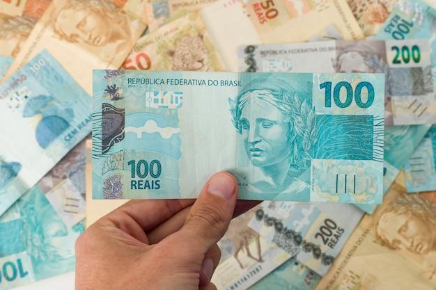 Dinheiro brasileiro, homem segurando notas de 100 reais.