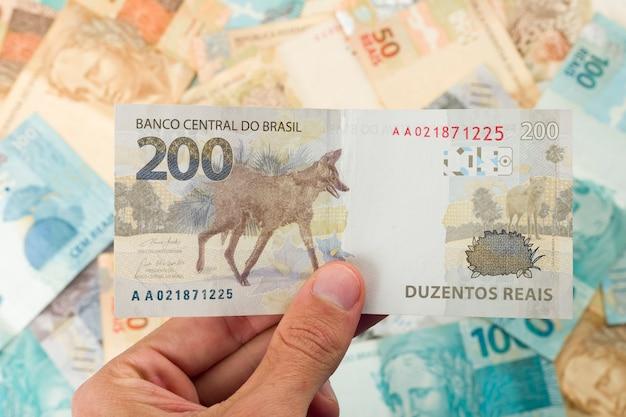 Dinheiro brasileiro, homem segurando notas de 200 reais.