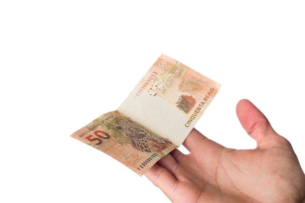 Dinheiro brasileiro, homem segurando notas de 50 reais isoladas no branco.
