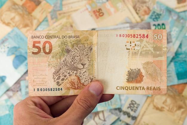 Dinheiro brasileiro, homem segurando notas de 50 reais.
