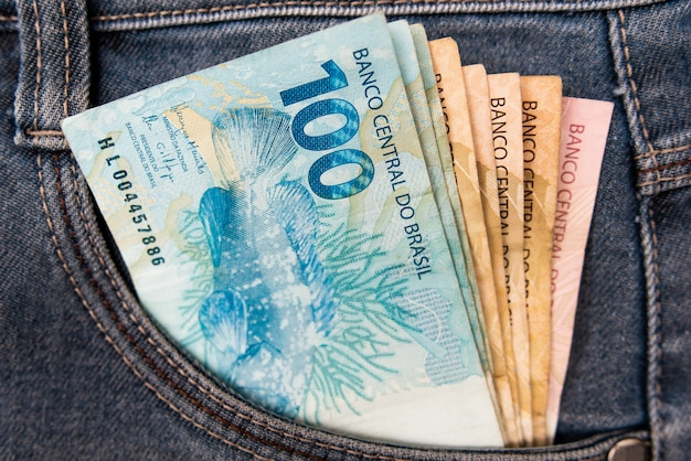Dinheiro brasileiro no bolso da calça jeans, conceito de finanças. moeda brasil