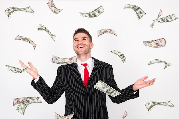 Dinheiro caindo de cima homem na suíte de braços abertos