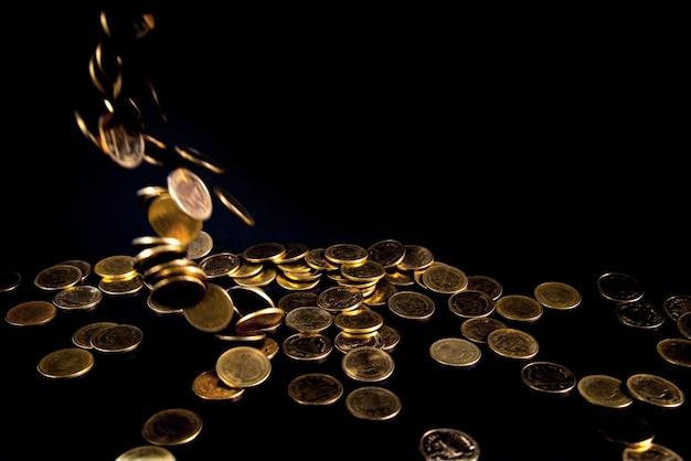 Dinheiro caindo de moedas de ouro em fundo escuro