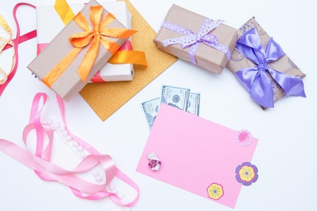 Dinheiro, caixas de presentes e cartão postal em um fundo branco