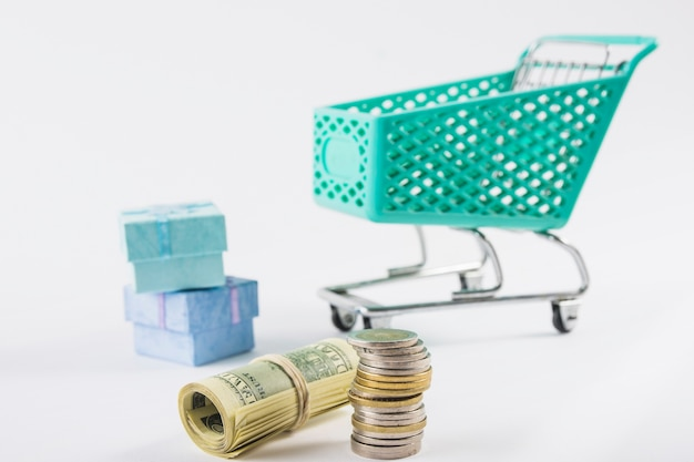 Dinheiro com carrinho de supermercado pequeno na mesa