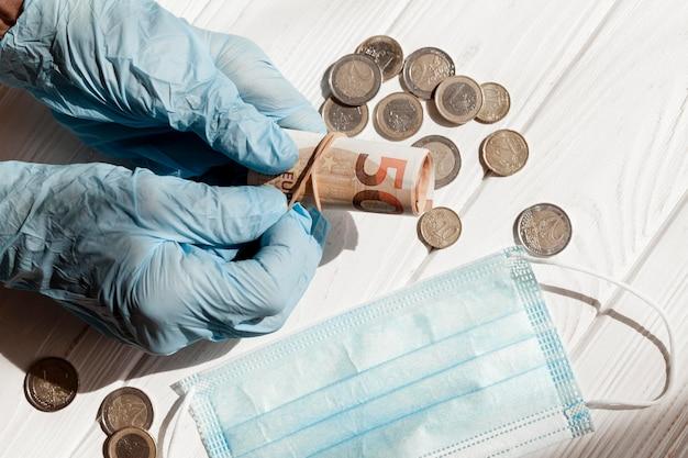 Dinheiro com luvas de proteção e máscara médica
