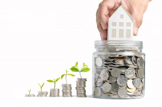 Dinheiro crescente - mão homem segurando modelo de casa em moedas em frasco de vidro
