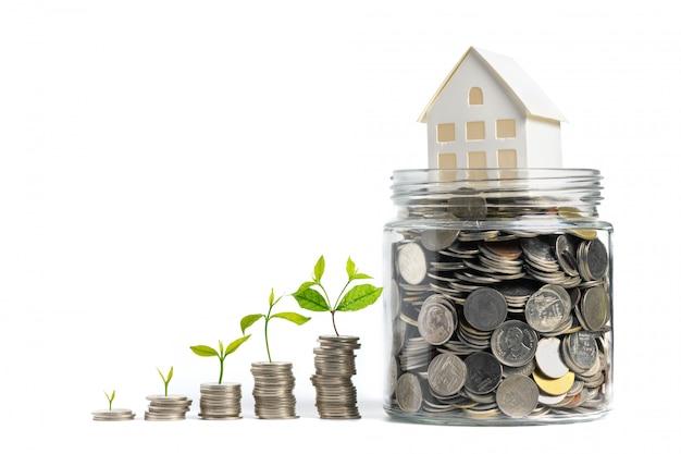 Dinheiro crescente - planta em moedas com modelo de casa em moedas em frasco de vidro isolado