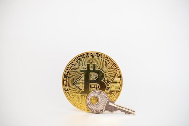 Dinheiro, criptomoeda financeiro e conceito de segurança. moeda de ouro bitcoin com chave de prata em fundo branco.