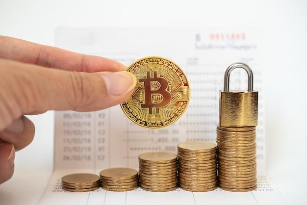 Dinheiro, criptomoeda financeiro e conceito de segurança. moeda de ouro bitcoin na mão do homem com pilha de moedas e fechadura com chave mestra na caderneta bancária.