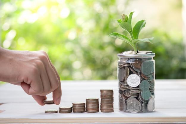 Dinheiro da economia e conceito do investimento pela mão masculina que põe as moedas do dinheiro que empilham para o crescimento do negócio.