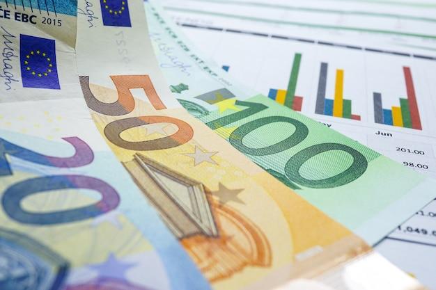 Dinheiro das cédulas do euro no papel de fundo do gráfico da carta.