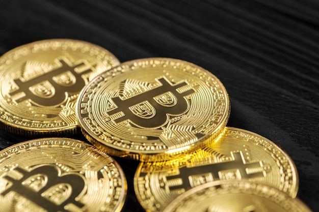 Dinheiro de bitcoin ouro na mesa de madeira. moeda criptográfica eletrônica
