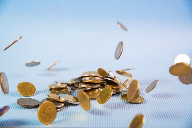 Dinheiro de moedas caindo no fundo azul